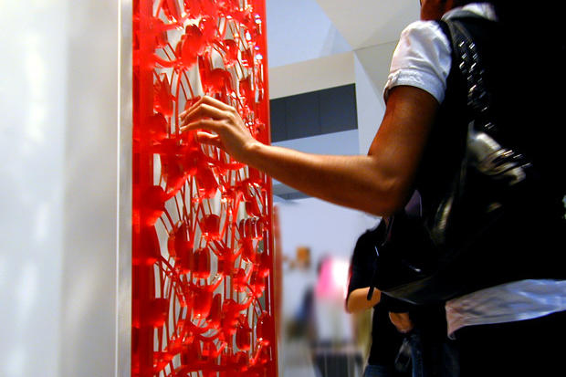 Designer touching decorative laser cut panel at IIDEX Interior design show 2007 in Toronto - Art Signs Company.