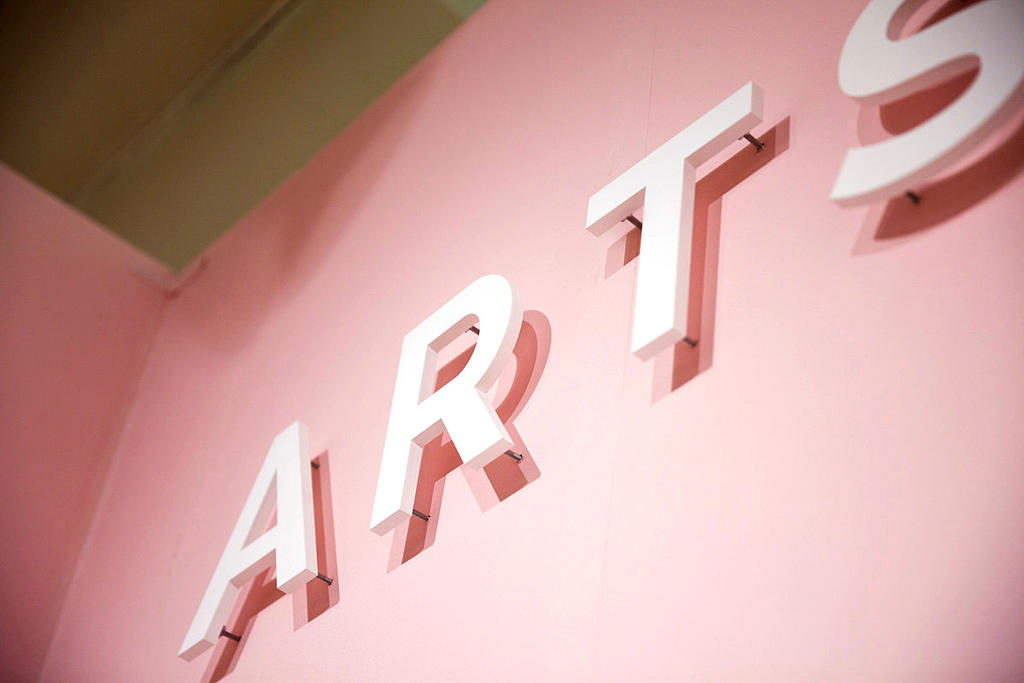 White plastic sign letters raised off pink color art show wall that say ART