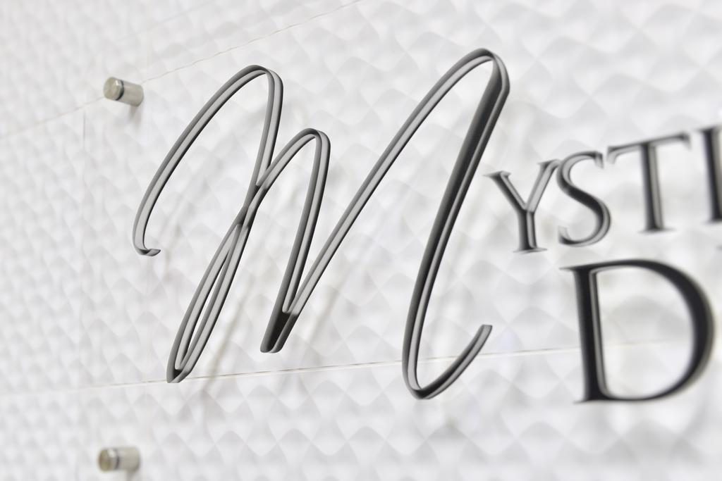 Dental Office Reception Sign Cursive Letter M on Textured Wall