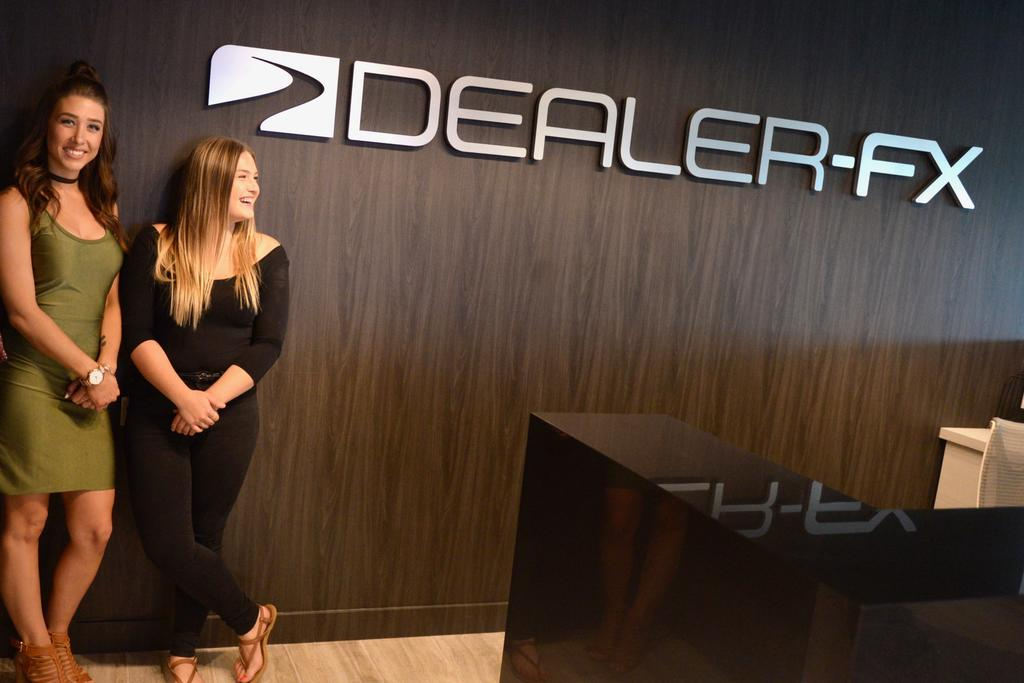 3D office reception sign for Dealer-FX on wooden reception wall with Becky Duncan and Jessie Mitchell
